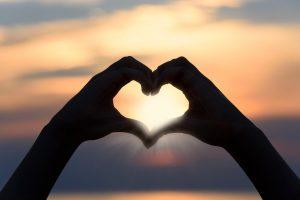Heart hands against a sunset