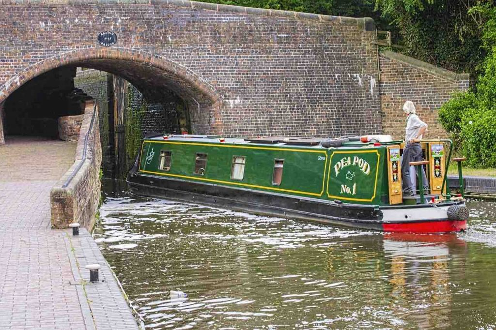 Man steering a narrow boat through a tunnel