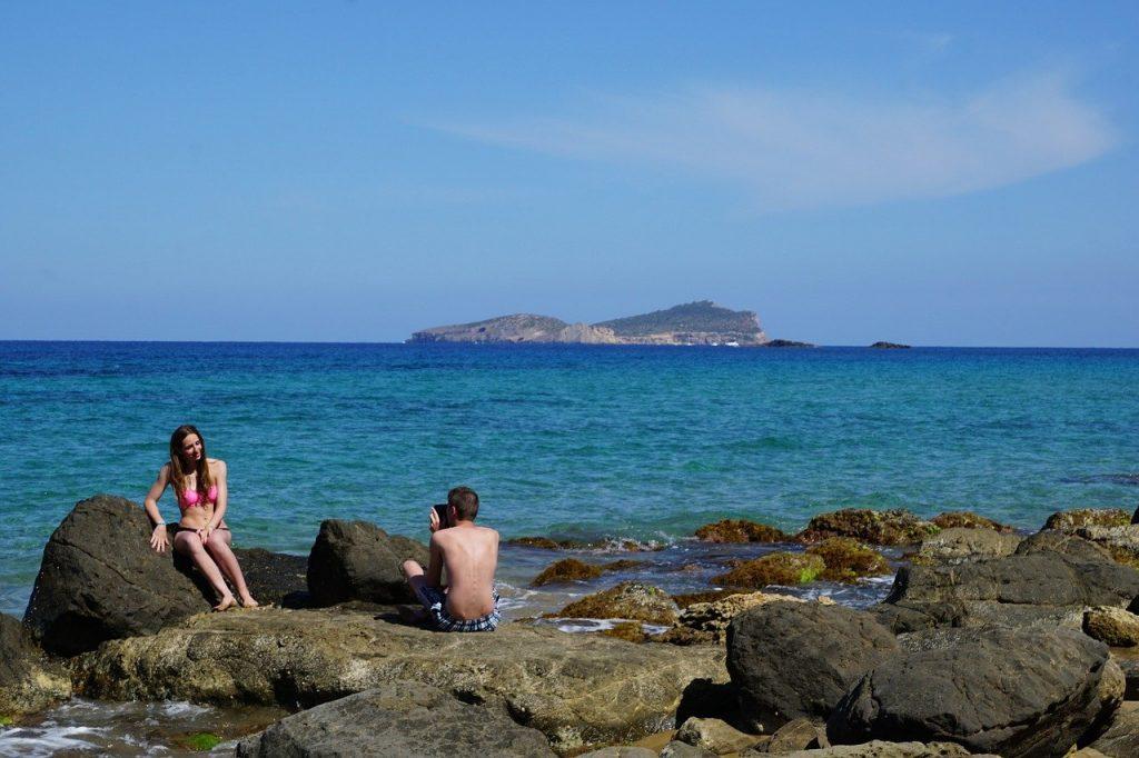 Man taking a woman's photograph on an Ibiza beach